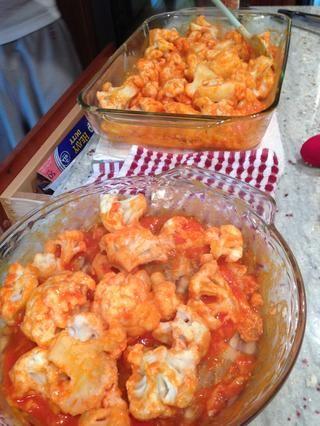Una vez que las alas se hacen cocer, sacarlos y añadir la mezcla de salsa picante. (No apague el horno)