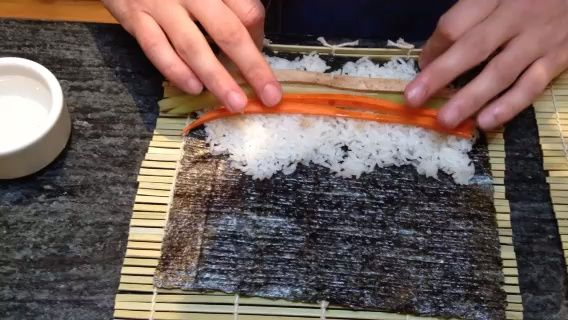 Utilice la estera de bambú sushi rodar cuidadosamente el sushi para que's tight. You'll want to seal the end by moistening your finger in a dish of water. This might take a few tries to get the hang of.