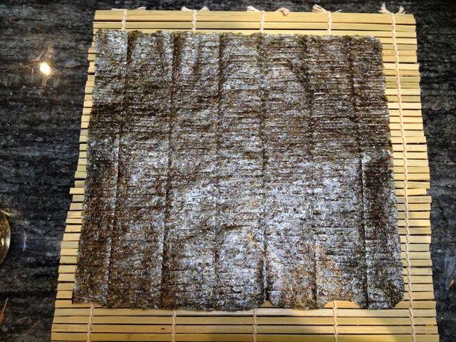 Obtener una hoja de nori (papel algas secas) y colóquelo con el lado brillante hacia abajo en el lado plano de una esterilla de sushi.
