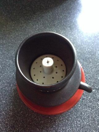 Añadir 3 cucharadita de café en el gotero. Presione suavemente (utilizando el prensador de café) para asegurar la uniformidad de café en la base del gotero.
