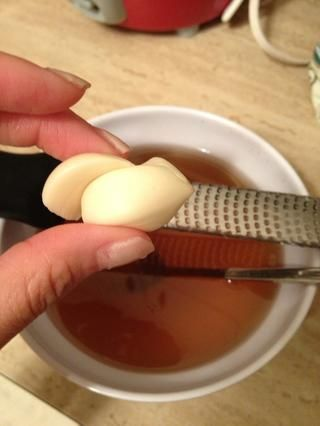 Mientras tanto, rallar 1 o 2 dientes de ajo sobre un tazón con la mezcla.