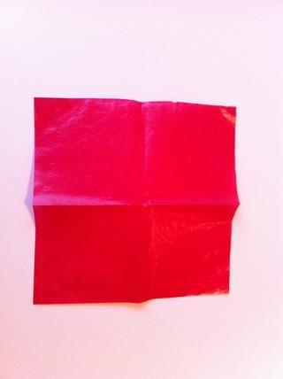 Dobla el papel por la mitad en la otra dirección para crear arrugas, a continuación, abrir el periódico y déjelo.