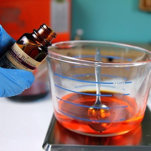 Ahora vierta cuidadosamente un recipiente de cera por molde. Puse la cera azul en el molde Lotus Blossom, la cera de color naranja en el molde de la fruta cítrica y la cera de color rojo en el molde de Apple.