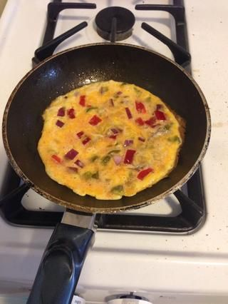 Después de un minuto o dos,'s time to flip. The trick to flipping an omelette is to wait until the bottom is cooked really well. You can see the top part is starting to solidify.