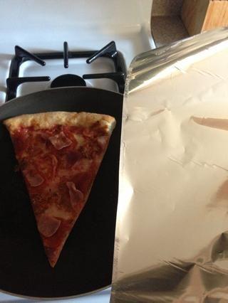 Arranca un trozo de papel de aluminio ligeramente mayor que la porción de pizza.