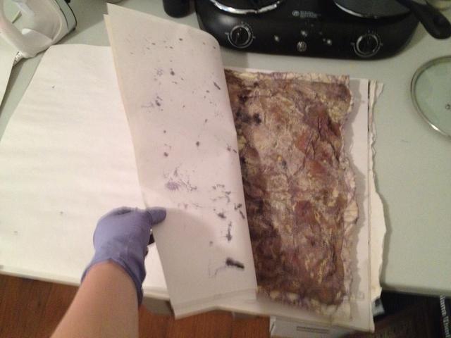 Arte Sandwich entre un par de hojas sueltas de papel de periódico y encender el hierro. Va a poner el hierro en las piezas superiores de papel para derretir la cera restante.