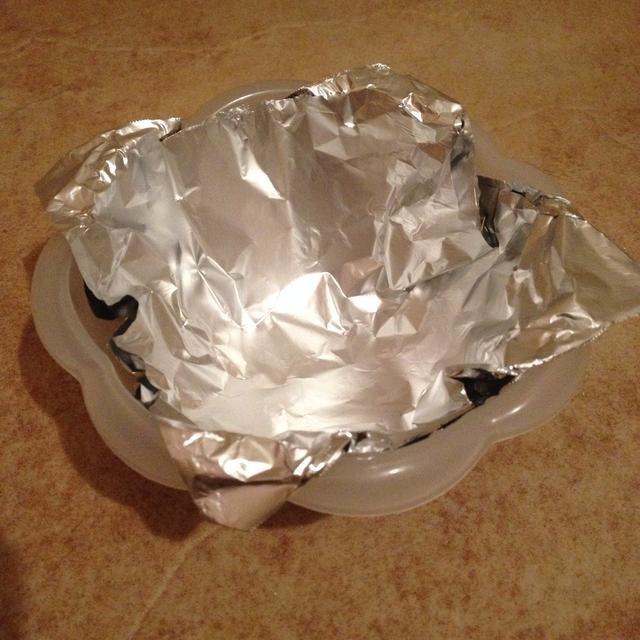 Cubra el recipiente con una hoja cuadrada de papel de aluminio.