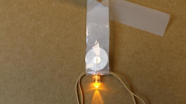 Ahora tomar otra tira de cinta (misma longitud) y firmemente la cinta justo encima de la pila de botón y se envuelve firmemente alrededor de nuevo para que no se deslice hacia fuera de la parte superior.