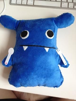 Utilice pegamento para adherir los ojos a la muñeca's face and use running stitches to sew the mouth and teeth.