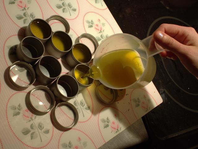 Con cuidado, vierta un poco de la mezcla de aceite en cada mini lata.