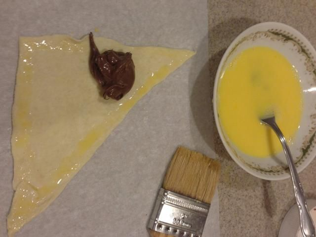 Cepille su lavado de huevo batido (1 huevo batido con un poco de agua) en los bordes del triángulo para asegurarse de que se'glue' the croissant together!