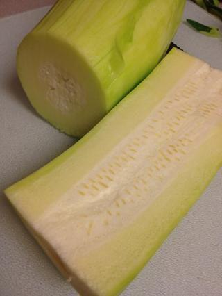 Cortar el calabacín en trozos manejables para que pueda quitar el centro esponjoso que contiene las semillas.