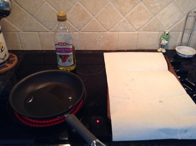 Prepara su puesto de trabajo, una sartén grande con aceite de cocinar y hornear hoja caliente forrado con papel toalla.