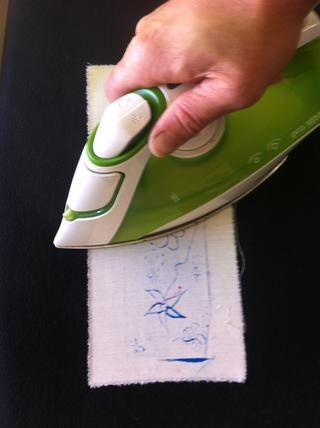 Hierro sobre la tira de diseño boca abajo. Esto evita que la pintura se adhiere a la superficie urna caliente. El calor del proceso de planchado en realidad sella la pintura de forma más segura a la tela.