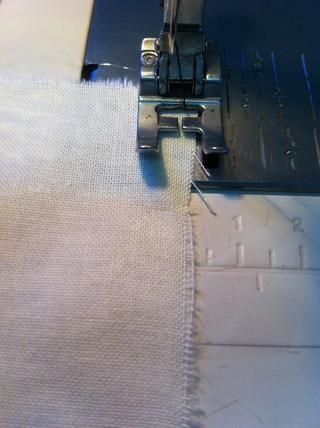 El primer paso es asegurar los bordes de la tela con puntadas zigzag. Fíjese en que el pie prensatela está en relación con el borde de la tela.