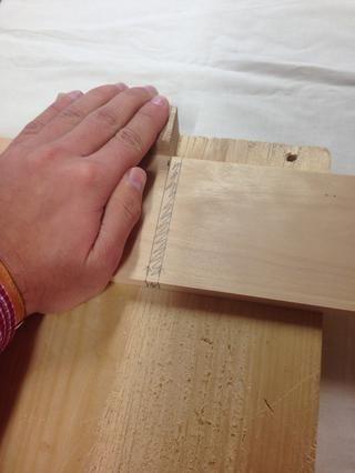Aguante la madera firmemente contra el tope con sus marcas de lápiz alineados como se muestra. Cuanto más se acerque a sus marcas hasta el borde del Alto de la Madera, más fácil es mantener al serrar.