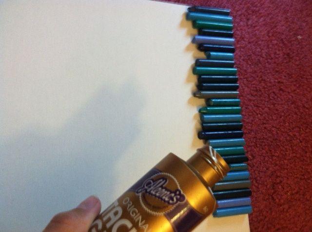 Utilice pegamento pegajoso para alinear sus lápices de colores en la parte superior del tablero.