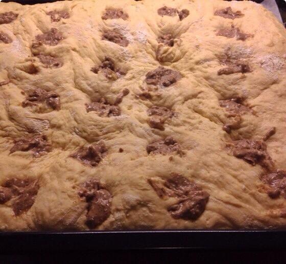Haga agujeros en la masa, ya sea con el dedo o con una cucharilla. Llene los agujeros con el relleno de queso crema. Tengo alrededor de 40 a 50 agujeros que significa 40-50 bollos.