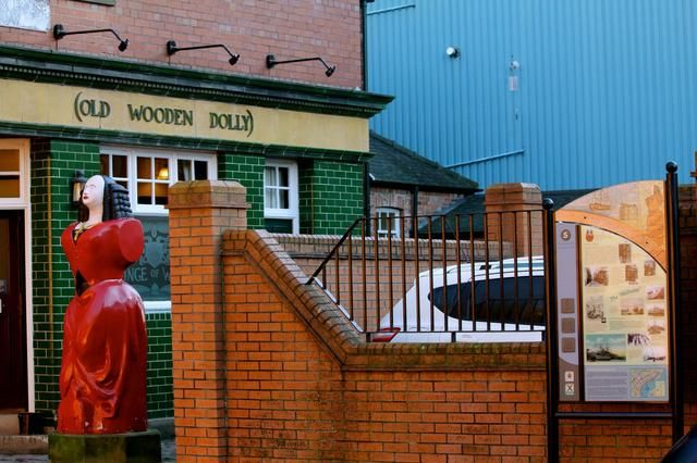 Grupo 5'The Wooden Dolly', difficult to miss, located right next to the Prince of Wales pub, the finely carved statue in red, contrasts sharply with the green tiles of the pub.
