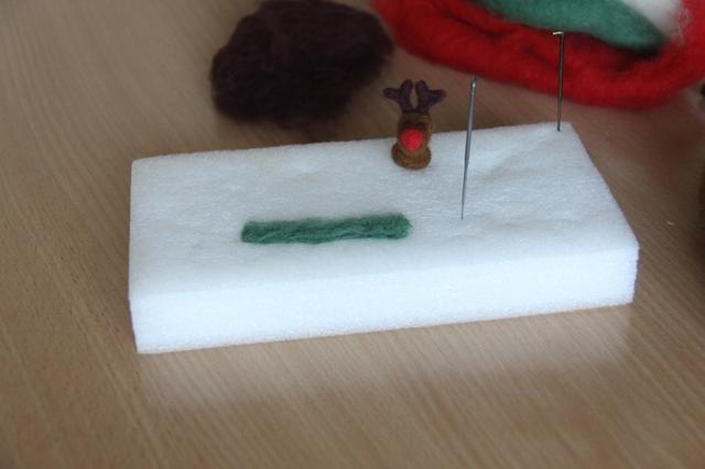 Use un poco de lana verde, se extendió en la plataforma para hacer la forma de una bufanda. Perforar superficialmente en el lugar que usted pone su lana. A su vez a otro lado y golpear hasta que se haga un pañuelo suave.