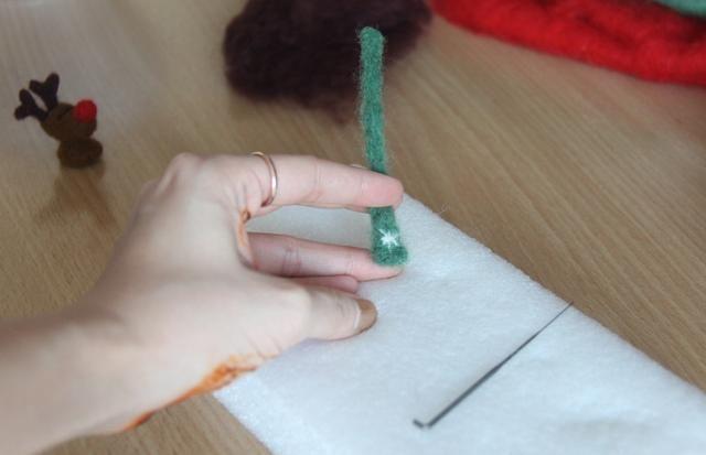 Use un poco de lana blanca para decorar la bufanda y luego coloque el pañuelo para el cuello de Rudolf.