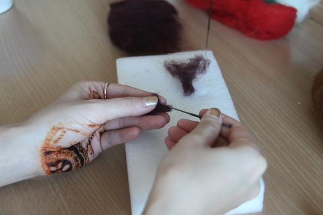 Utilice unas partes iguales de lana de color marrón oscuro para formar 2 cuernos. Deja el final sin tocar.