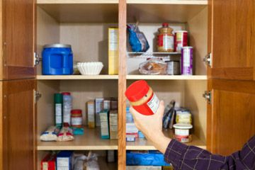 Cierre plano de una mujer's hand taking a jar of peanut butter out of an open pantry.