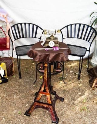 Don't forget the photo booth. As a backdrop I used a tablecloth. Small side table and antique telephone will set the atmosphere. I added some shopping bags and Eiffel Tower