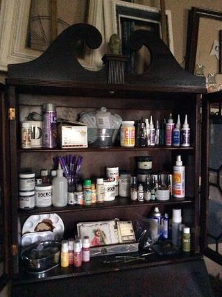La mitad superior de un escritorio de la secretaria de edad alberga pinturas, adhesivos y tal.
