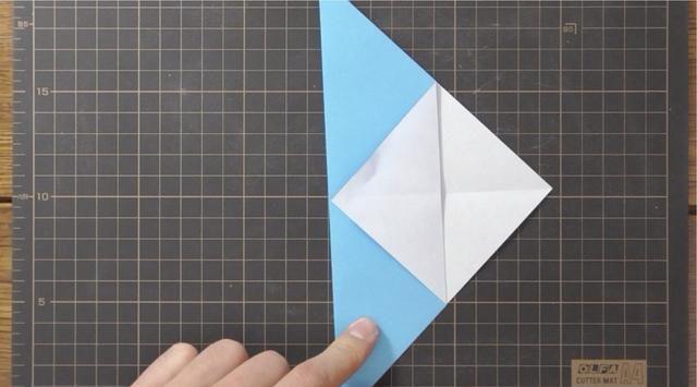 Dobla la esquina derecha de la capa superior a la izquierda para tocar borde doblado.