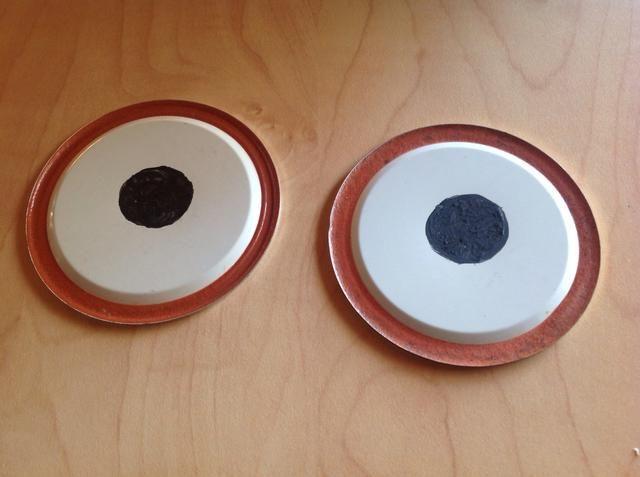 En la parte inferior de las tapas de los frascos de conservas, hacer un gran círculo negro con pintura negro. Deje secar.