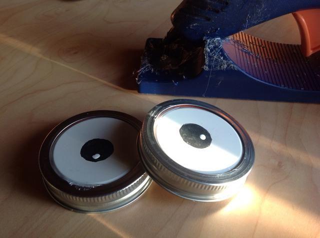 Utilice pegamento caliente para pegar las tapas en el interior de los anillos de tarro de conservas.