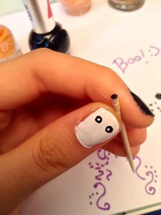 A continuación, utilice el lado puntiagudo del palillo para puntear dos pequeños círculos blancos en el interior del otro negro. Esto será los ojos de fantasmas :)
