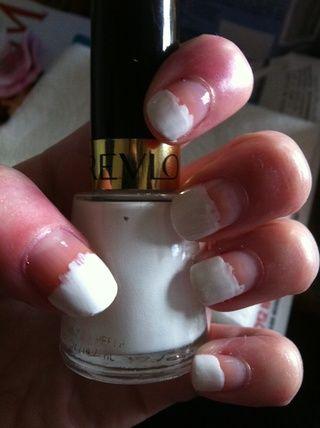 Pintar dos manos sucias de esmalte blanco a media altura de las uñas.