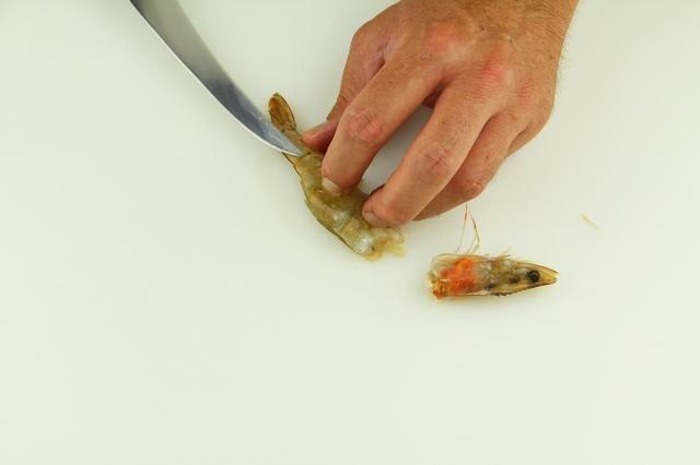 Enderezar la cola de camarón presionando hacia abajo con su dedo medio y alisado con el pulgar y el dedo anular. Coloque el cuchillo en la parte plana de la punta de la cuchilla de la cola y de inserción.