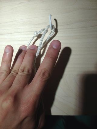 Pasar el extremo libre de la sutura a través del bucle. ¡Prepárate para agarrarlo con el pulgar y el dedo medio.