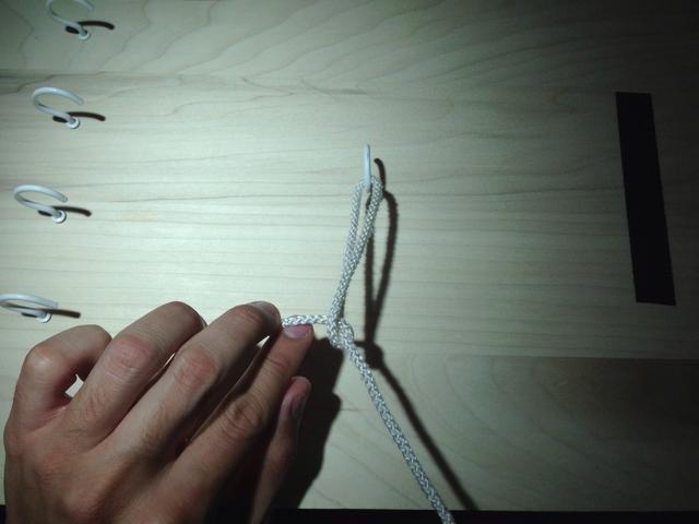 Coge el círculo entre el índice y el dedo medio y tire de ella a través del bucle.
