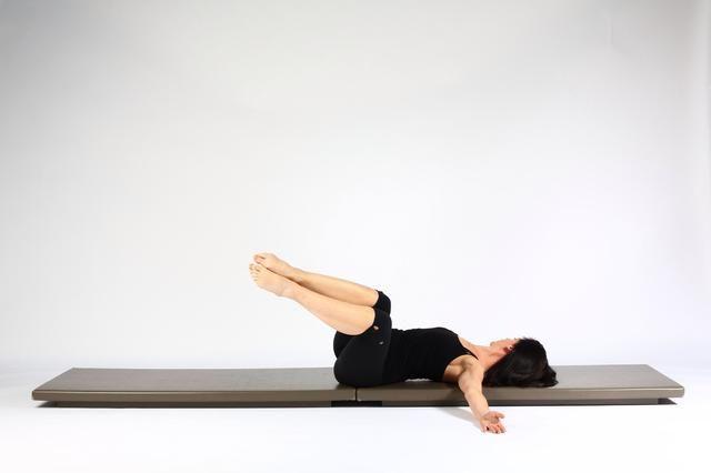 Rotación espinal. Dibuje las rodillas y los tobillos a la izquierda y girar la cabeza hacia la derecha