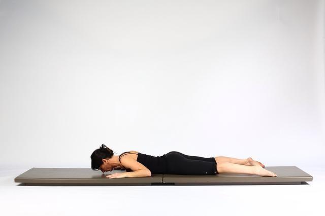 Volver Lie Extensión boca abajo con los codos por su lado y las manos en la colchoneta en línea con los codos. Mantenga distancia piernas hop o más separados.