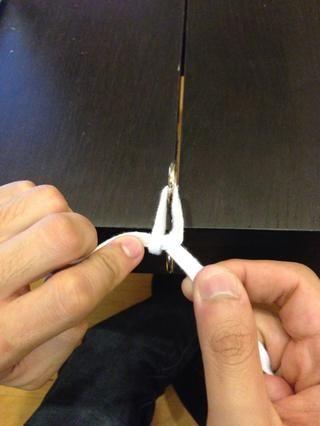 Coge el extremo libre con su mano no-lanzamiento. Al aplicar tensión igual y opuesta, empujar el nudo hacia abajo con su dedo índice en la sutura aprox. 1 cm desde el nudo.