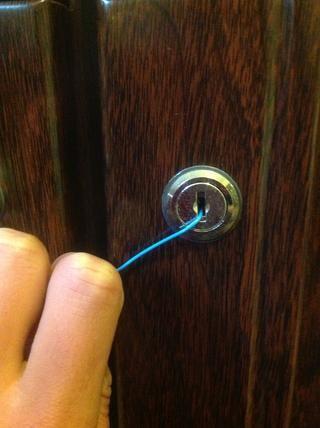 Inserte el clip de papel enganchado en la cerradura. Aplique presión hacia abajo y tire de ella en la dirección de las vueltas de tope