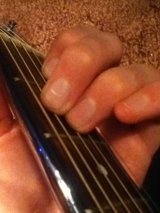 A continuación, poner el dedo anular en el segundo traste, cuarta cuerda. A continuación, poner el dedo medio derecho por encima de eso.