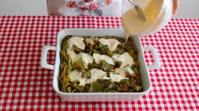 Colocar las judías verdes en una bandeja de horno y añadir la crema en la parte superior. Calentar el horno a 200 ° C y hornear los frijoles durante 10 minutos.