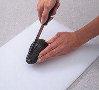 Gire el aguacate alrededor del cuchillo, por lo tanto cortar por la mitad.
