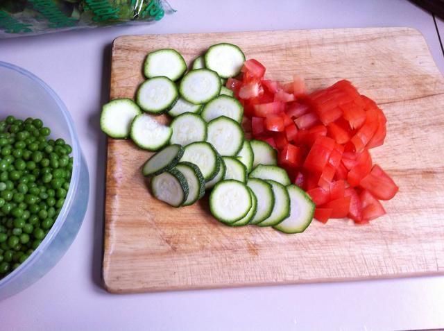 Cortar el calabacín y el tomate y añadir a los guisantes.