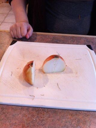 Con la parte plana hacia abajo en la tabla de cortar, cortar la cebolla en dos partes iguales