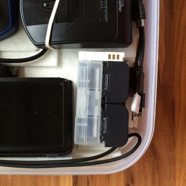 Al lado de la cámara de fotos, hay una caja de / MicroSD-Tarjetas, 2 baterías y cámaras de vídeo de un batería de la cámara de fotos de 8 SD. usted'll also notice that on the side, there was room for spare charging cables.