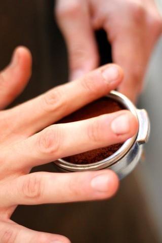 Use su mano y nivelar el espresso en una capa plana. Limpie cualquier exceso de café espresso de los lados de la canasta.