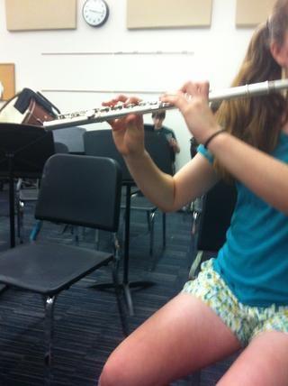 La flauta se celebrara señaló ligeramente hacia el suelo, pero cerca de paralelo.