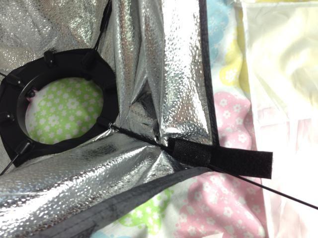 Sangrar la clavija en la toma de corriente en el ring mientras doblando el material softbox más cerca del anillo.